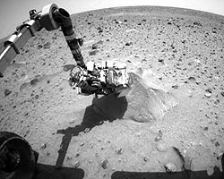 Spirit's arm reaches down to the Martian soil to investigate a rock.