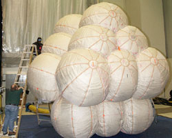 Workers prepare the Mars Exploration Rover airbag system for testing at the Space Power Facility.