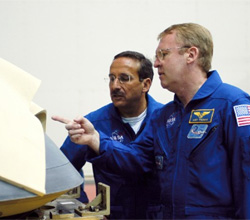 STS-114 mission specialists Charles J. Camarda (left) and Andy Thomas look at the nose cap from Space Shuttle Atlantis.