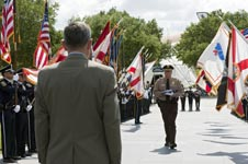 James K. Loftus, director of the Miami-Dade Police Department, prepares to present the U.S. Honor Flag to Bob Cabana, director of NASA's Kennedy Space Center, with the color guard looking on.
