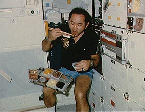 Astronaut eating in space using chopsticks