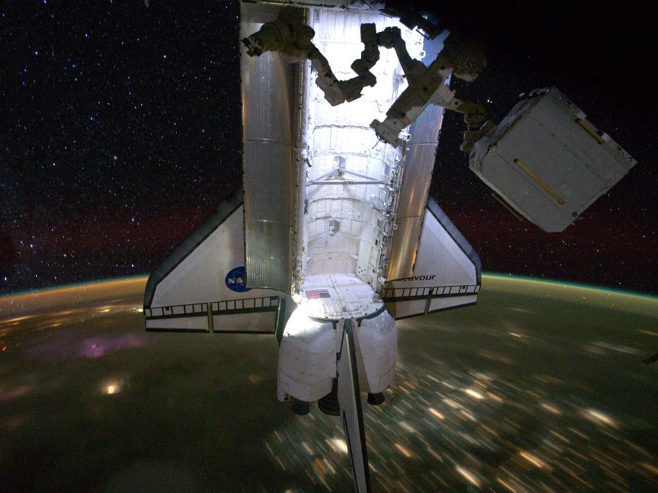 Backdropped by a night time view of the Earth and the starry sky, the Space Shuttle Endeavour is docked at the International Space Station on May 28, 2011.
