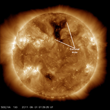 A coronal hole, the darker area in the center of the northern hemisphere, is the source of high-speed solar wind stream flow.