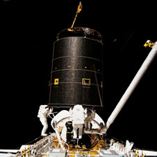 STS049-91-026: Three astronauts hold onto Intelsat VI