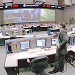 A man stands in front of his desk at the Mission Control Center