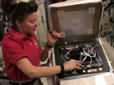In this video still, NASA astronaut Cady Coleman shows the spider habitat.