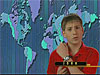 A boy points to his wristwatch as he stands in front of a world map divided into time zones