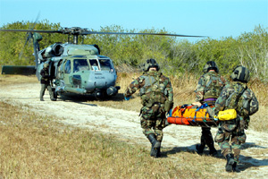 A rescue team carries a crew member toward the helicopter for transportation to a local hospital.