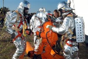 Silver-suited emergency personnel tend to a crew