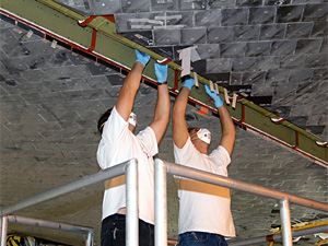 Technicians work on insulation tiles