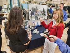 NASA Deputy Administrator Lori Garver (center, right) discusses the Electron Beam Freeform Fabrication system with engineer Karen Taminger (center, left)
