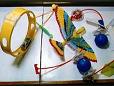 Toys resting on a table are a friction car and loop track, paper eagle, and balloon helicopters