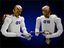 Two humanoid robots hold hand tools