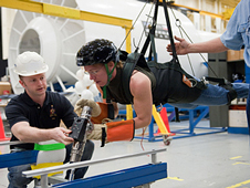 Astronaut Sandy Magnus hangs in a harness during training