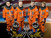 The STS-135 crew poses in orange suits in front of a picture of the U.S. flag