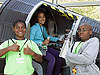 Two boys stand next to a girl who is inside a space capsule simulator