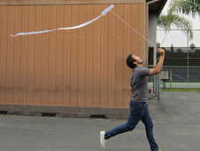 A young man runs with a small kite