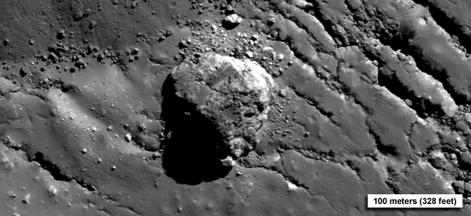 vertical view of large boulder on peak in Tycho Crater