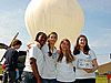 Four girls stand in front of a weather balloon