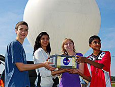 Four students stand in front of a weather balloon holding their experiment in a white box with a NASA logo on it