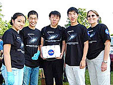 Four students and their teacher stand outdoors, with their experiment in a white box with a NASA logo on it