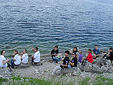 12 students sitting on rocks beside a lake