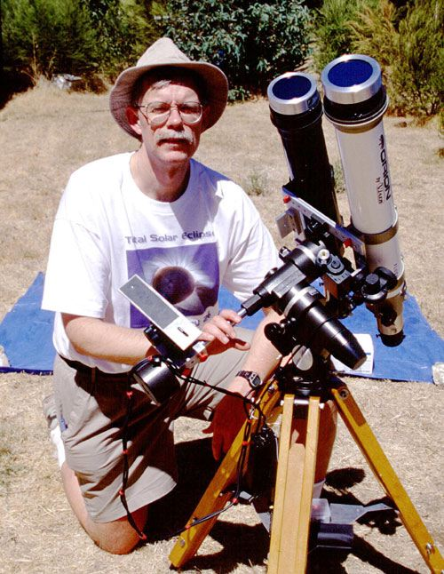 Fred Espenak poses by his telescope