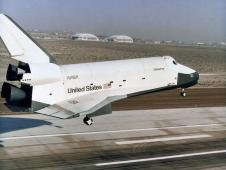 The prototype space shuttle enterprise settles toward the main runway at Edwards Air Force Base.