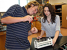 Two students setting up experiment