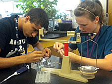 Two students preparing bacteria samples