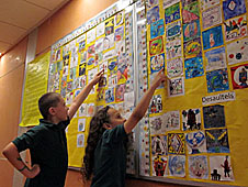 Two students point at a bulletin board