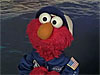 Elmo dressed in a blue flight suit