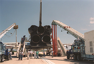 A convoy of landing support vehicles gather around Discovery after a landing.