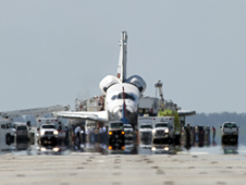 A convoy of safing and emergency vehicles surrounds a space shuttle on the runway