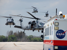 Helicopters with medical personnel aboard hover over Kennedy Space Center's Shuttle Landing Facility