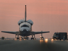 Landing convoy equipment is hooked up to a space shuttle on the runway just before sunrise