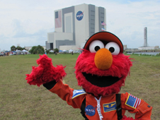 Sesame Street's Elmo stands in front of a large NASA building