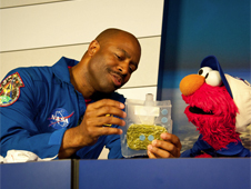 Leland Melvin shows Elmo a bag of space food