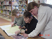 Alice Shaw, Diane Bowen and Ben Hauptman looking at a lithograph
