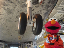 Sesame Street's Elmo under space shuttle with landing gear nearby