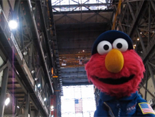 Sesame Street's Elmo stands inside a large NASA building