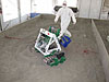 A student walks behind a robot that is scooping soil