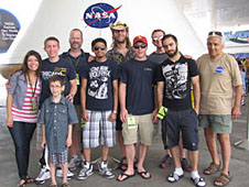 Robotics team stands in front of a space capsule