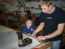 College student measures a gear while a young boy looks on