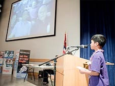 A student asking a question into the microphone and a video image of astronauts on the wall in front of him