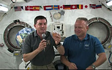 Mission Specialist Rex Walheim, with Pilot Doug Hurley at his left, holds a microphone and space food packet