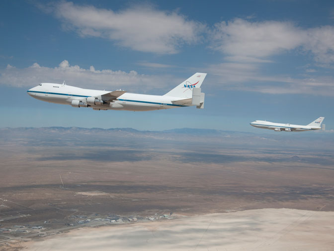 NASA's two modified 747 Shuttle Carrier Aircraft were captured by photographer Carla Thomas as they flew in formation over Rogers Dry Lake at Edwards Air Force Base. NASA Dryden Flight Research Center's complex of buildings can be seen on the edge of the lakebed immediately below NASA 911.