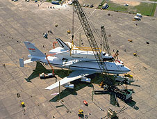 The cranes and sling practice lifting a shuttle.