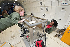 Two women float near an experiment inside an airplane