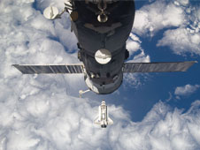 Backdropped by Earth, Discovery approaches the International Space Station during STS-133 rendezvous and docking operations. Already docked to the station is a Russian Progress spacecraft.